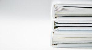 Imagen de libros y archivador apilados en orden